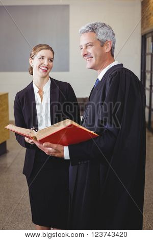 Happy male lawyer with book smiling while standing by female colleague in office