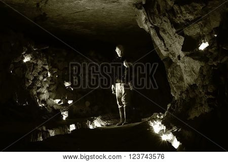 Spelunkers standing in chamber in abandoned mine in Wiltshire, UK. A cavernous space known as the Cathedral, in Box Freestone Mine which contains 90km of tunnels below Wiltshire