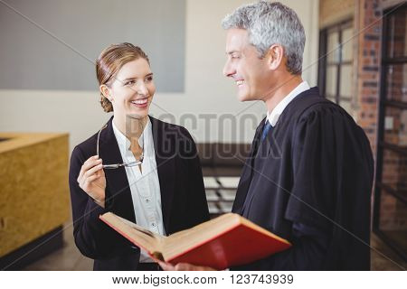 Happy male lawyer with book standing by female colleague at office