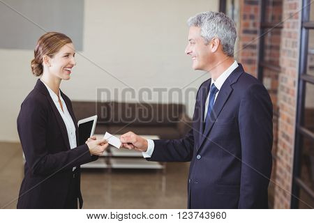 Happy businesswoman giving business card to client in office