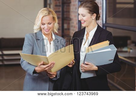 Happy businesswomen holding documents while discussing at office