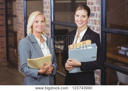Portrait of smiling businesswomen holding documents while discussing at office