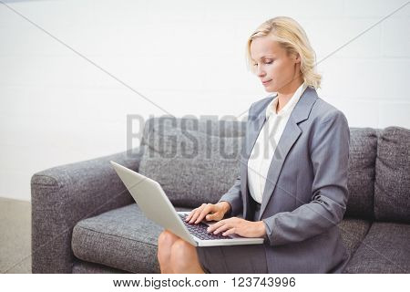 Bussinesswoman working on laptop while sitting on sofa at office