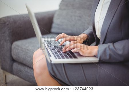 Midsection of bussinesswoman working on laptop while sitting on sofa at office
