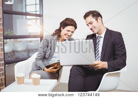 Cheerful business people using technology while discussing at office