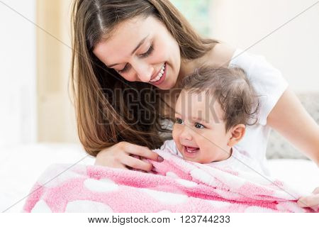 Smiling mother and baby with blanket on bed at home