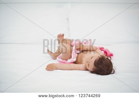 Baby holding blanket while lying on bed at home