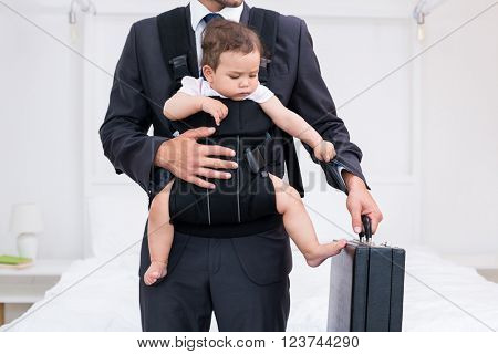 Midsection of father carrying baby while holding briefcase at home