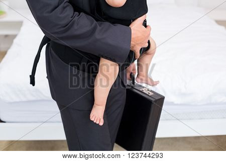Midsection of father carrying baby with briefcase at home