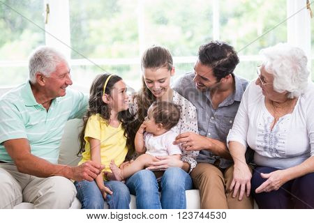 Smiling family with baby while sitting on sofa at home