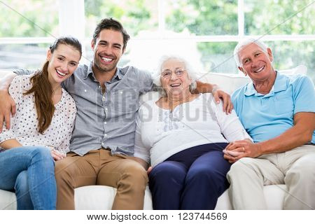 Portrait of smiling multi-generation family sitting on sofa at home