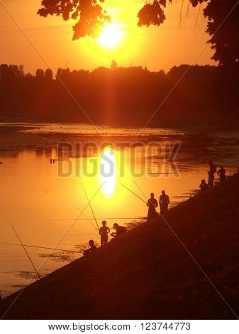 Fishermen and sunny summer evening on the river