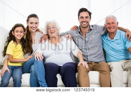 Portrait of smiling family with arm around while sitting on sofa at home
