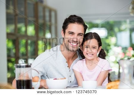 Portrait of smiling father and daughter at table in home