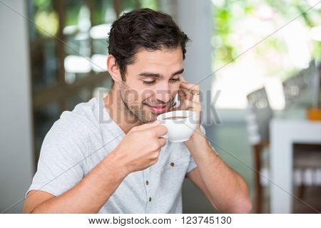 Smiling man having coffee while talking on mobile phone at home