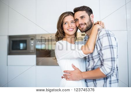 Happy couple looking away while embracing in kitchen at home