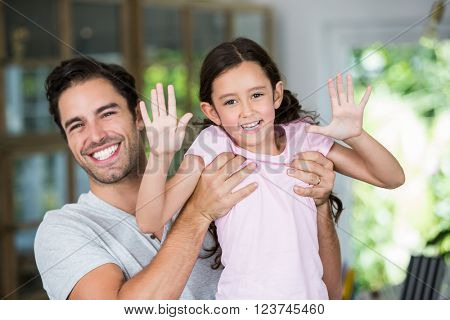 Portrait of smiling father carrying daughter at home