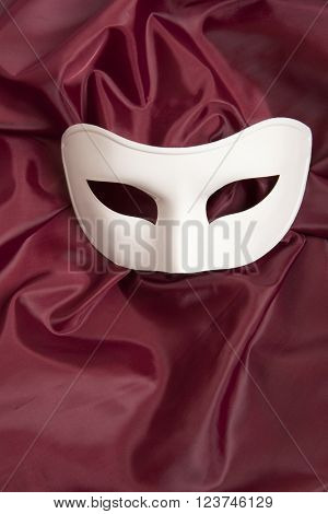 White theatrical mask and red silk fabric