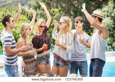 Group of friends raising their hands and enjoying near pool