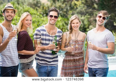 Group of friends enjoying while having champagne near pool