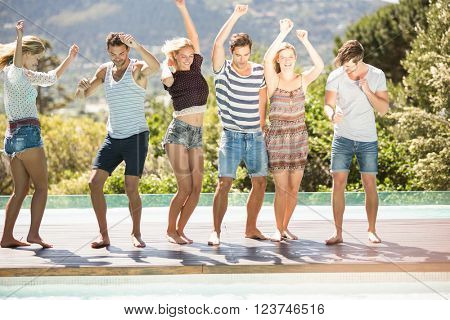 Group of friends enjoying while dancing at poolside