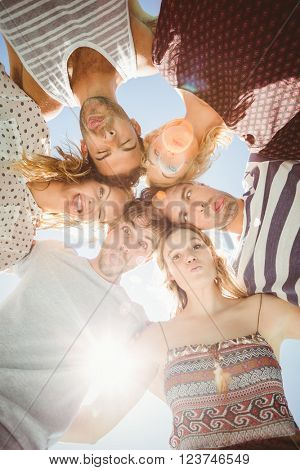Group of happy friends making funny faces while forming a huddle against sky