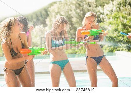 Happy friends doing water gun battle near swimming pool