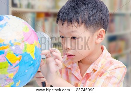 Asain boy using magnifying glass to see map in library