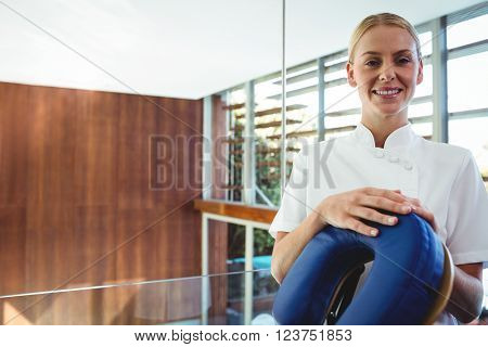 Portrait of masseuse next to massage chair at spa