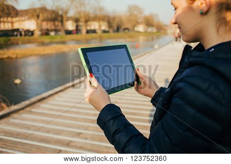 Smiling young woman student taping on tablet using tablet in a city park near river.Young smiling student outdoors with tablet.Life style.City