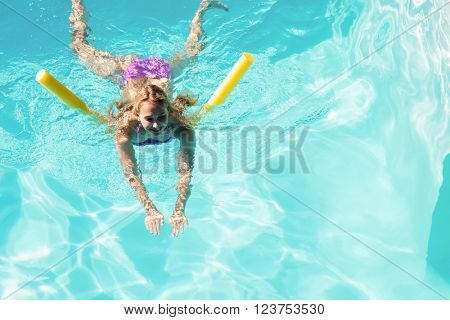 Woman swimming in swimming pool on a sunny day