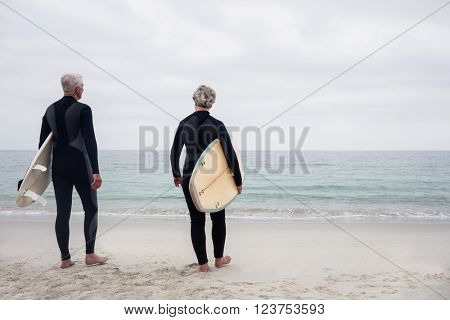Rear view senior couple in wetsuit holding a surfboard on the beach