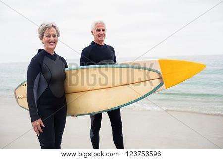 Senior couple with surfboard standing on the beach on a sunny day