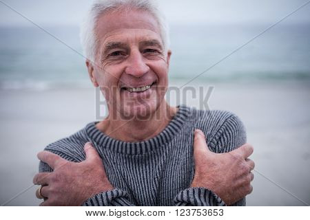 Portrait of senior man in sweater feeling cold on beach