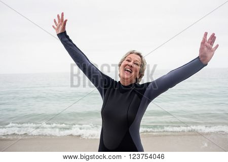 Happy senior woman standing on the beach with hands out stretched