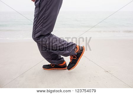 Man's foot while jogging on the beach on a sunny day