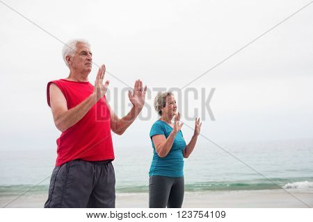 Senior couple exercising on the beach on a sunny day