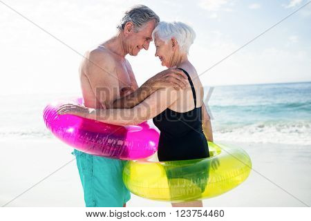 Senior couple in inflatable ring embracing each other on beach