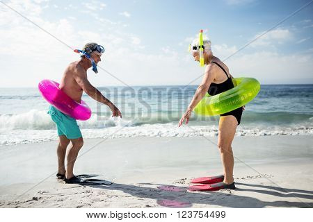 Senior couple with scuba gear and inflatable ring enjoying their holidays on beach