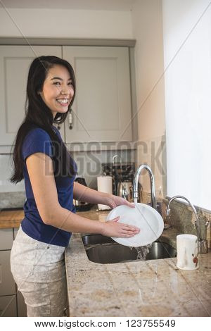 Portrait of happy woman washing up in the kitchen at home