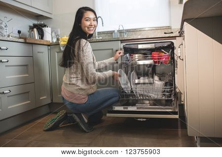 Portrait of woman in kitchen arranging plates in dish washer