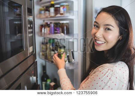 Portrait of woman checking her refrigerator at home