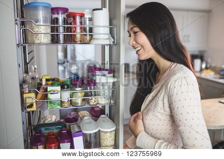 Young woman looking into the storage cabinet in kitchen