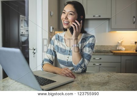 Happy woman using laptop while on call in the kitchen at home
