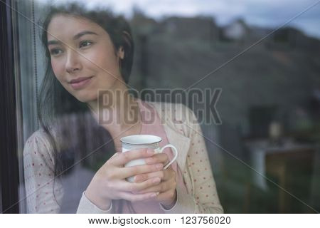 Happy woman holding a coffee cup and looking through window