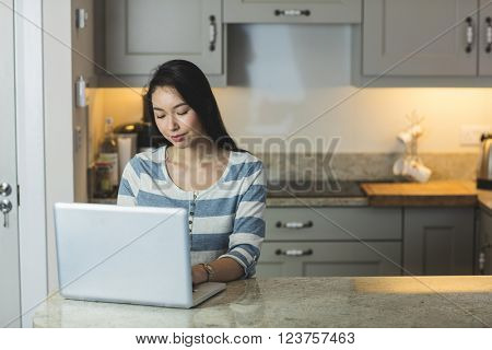 Young woman using a laptop in the kitchen at home