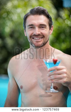 Portrait of a happy man with martini glass near pool