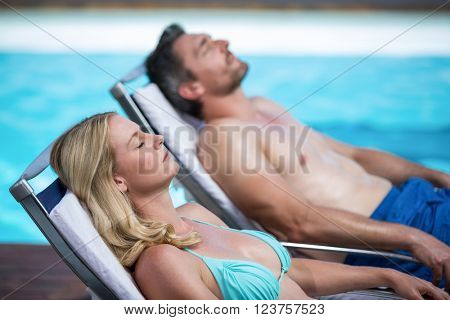 Couple relaxing on a sun lounger near pool