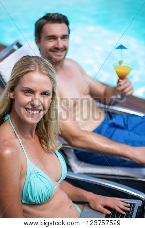Couple sitting near pool with a laptop and martini glass