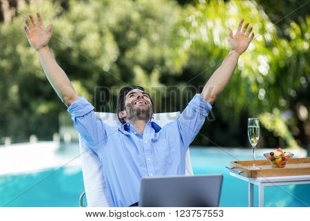 Excited man using a laptop near the pool